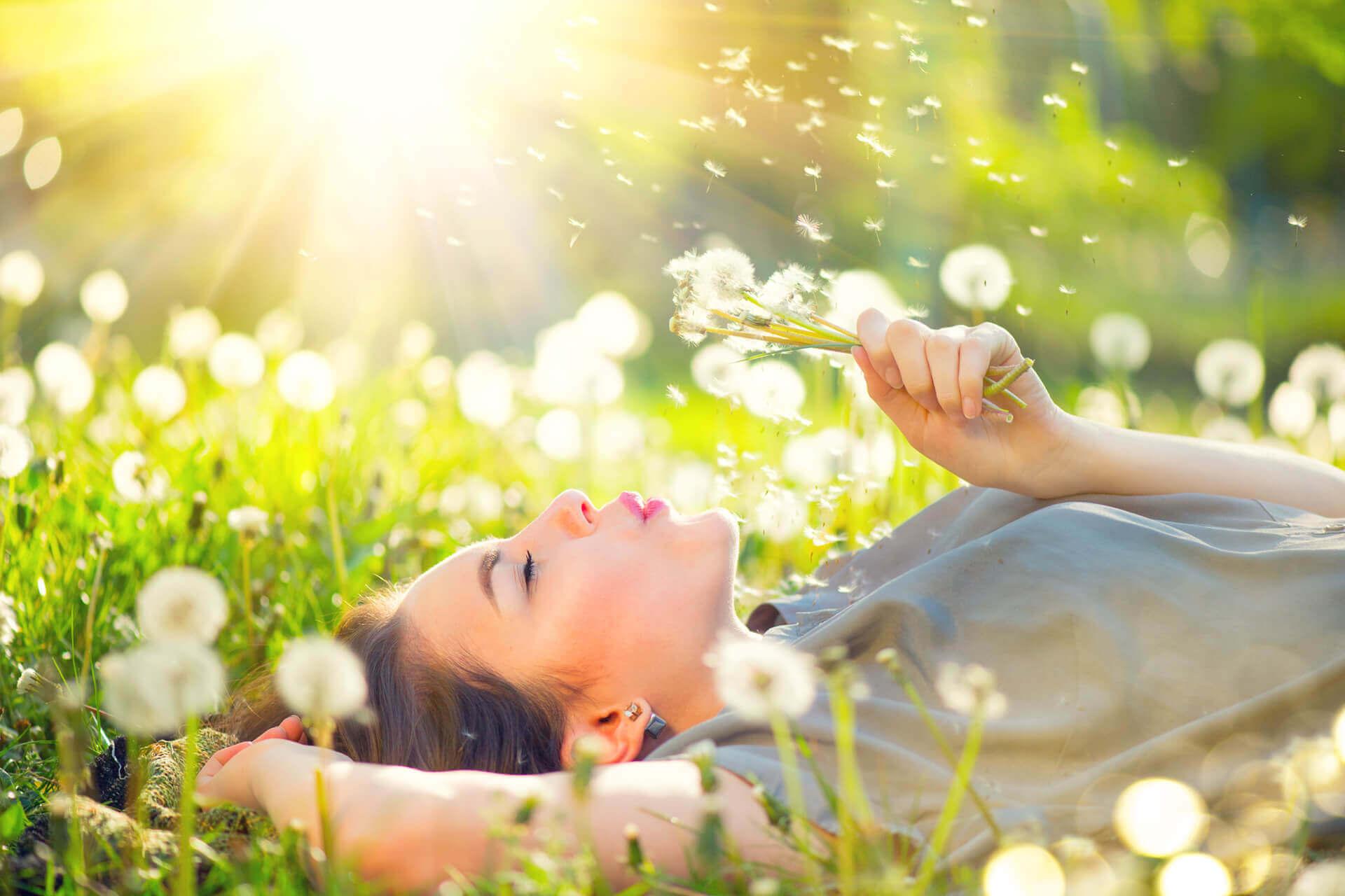Woman lying in meadow blowing dandelions