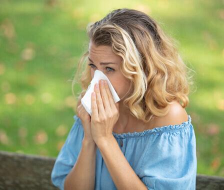 Blonde woman sneezing into kleenex in meadow
