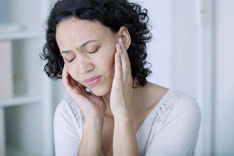 Woman with tinnitus holding hears