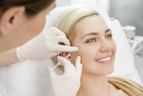 Woman having dermal filler injection